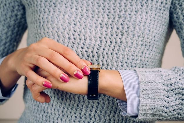 女性の手に革ストラップが付いている金の腕時計