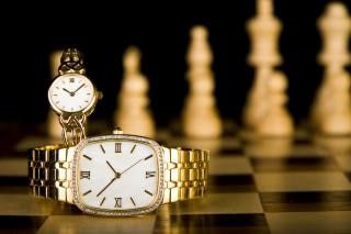 Gold watched on chess board