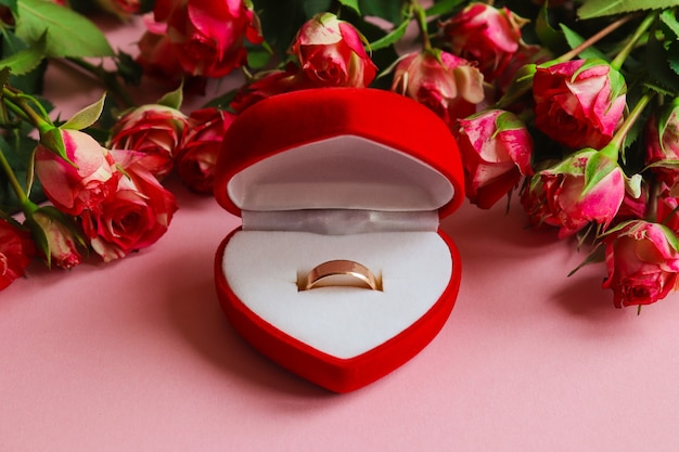 Gold wedding ring in gift box surrounded by flowers.concept of proposal,wedding,love,valentine's day