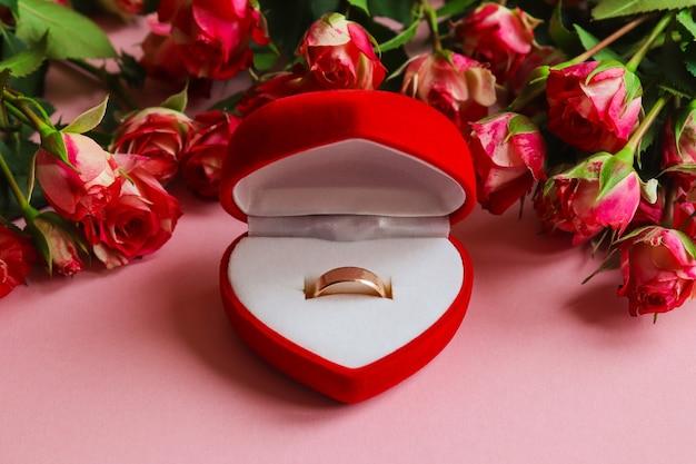 花に囲まれたギフトボックスの金の結婚指輪。プロポーズ、結婚式、愛、バレンタインデーのコンセプト