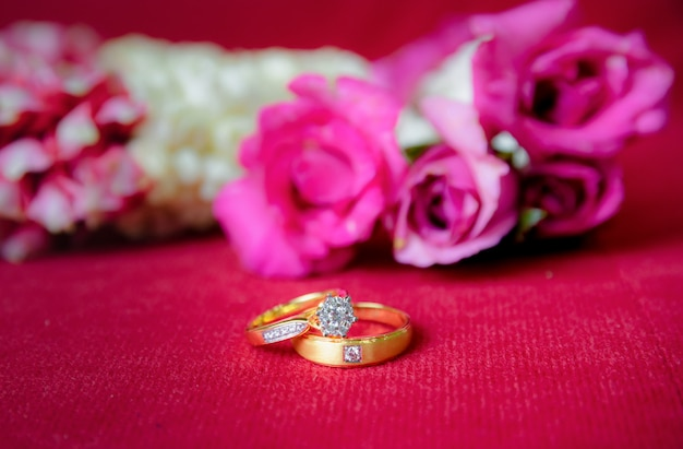 Gold wedding ring and red a roses