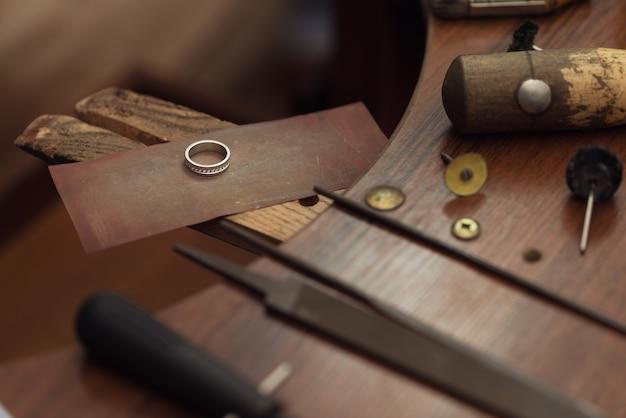 宝石商のブライダル結婚によって手作業で磨かれたダイヤモンド付きのゴールドの結婚指輪。