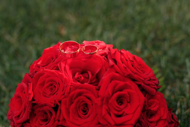 金の結婚指輪と草の上の赤いバラの花束