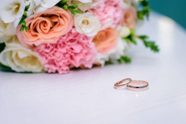 Золотые обручальные кольца и свадебный букет на белой поверхности