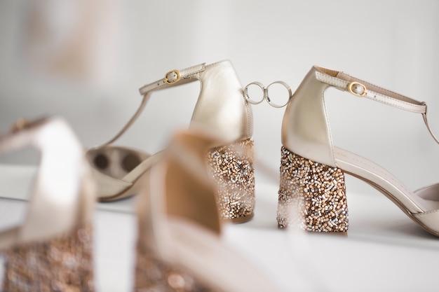 花嫁の結婚式の靴の間の金の結婚指輪
