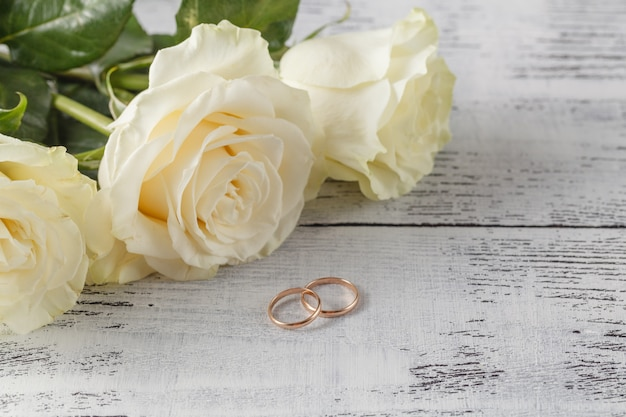Gold wedding rings on a bouquet of white roses