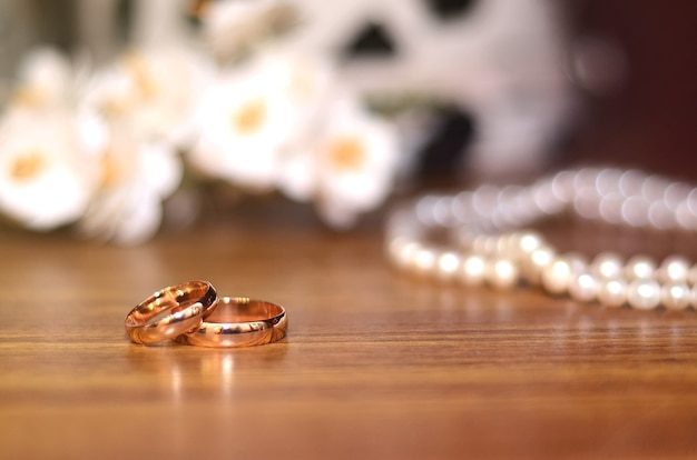 Gold wedding rings next to the bride's bouquet on a wooden table