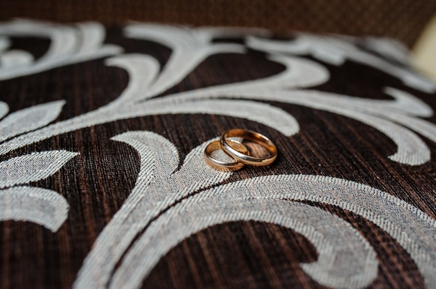 Gold wedding rings on brown fabric