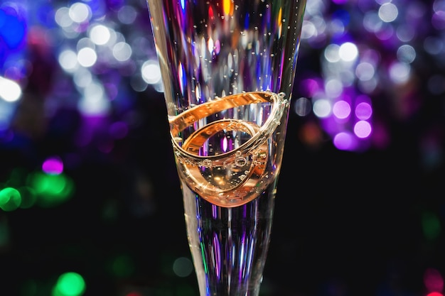 Gold wedding rings in champagne glass with bubbles on colored blurred background