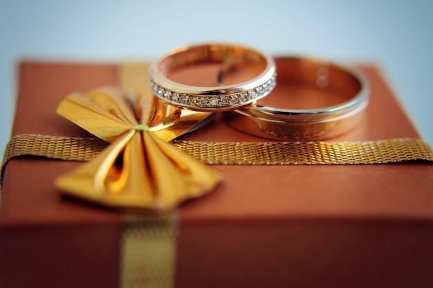 金の結婚指輪、クローズアップ。新郎新婦、マクロ写真をリングします。結婚式の属性と装飾。