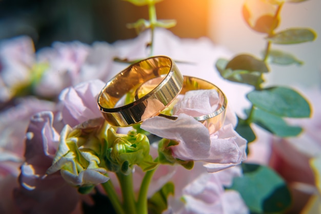 Gold wedding rings and delicate pink flowers, selective focus, close-up.