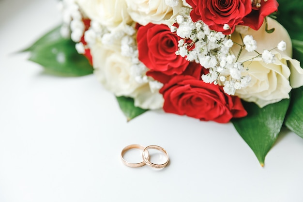 Gold wedding rings and flowers bouquet in white red colors lying on white background. declaration of love, spring. wedding card, valentine's day greeting. wedding rings. wedding day details.