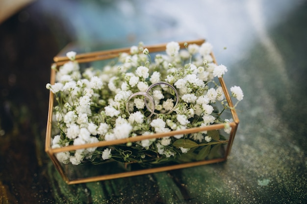 Gold wedding rings in a glass box with white flowers