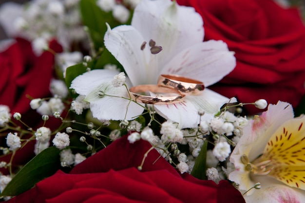 Gold wedding rings of the groom and the bride lie on a bouquet of the bride