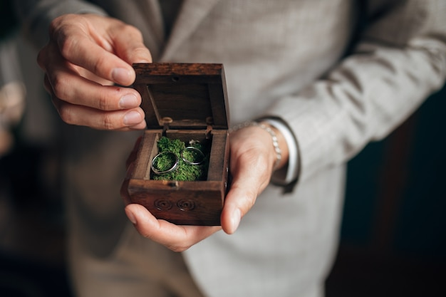 Gold wedding rings in the hands of groom