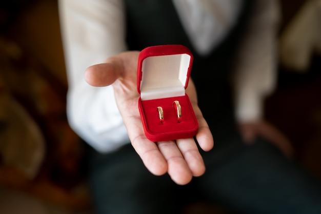 당신의 손에 있는 빨간 상자에 금 결혼 반지.
