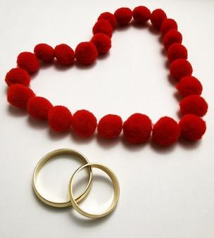 赤いハートのゴールドの結婚指輪。ハートに囲まれた白い壁に結婚指輪。愛と献身の象徴