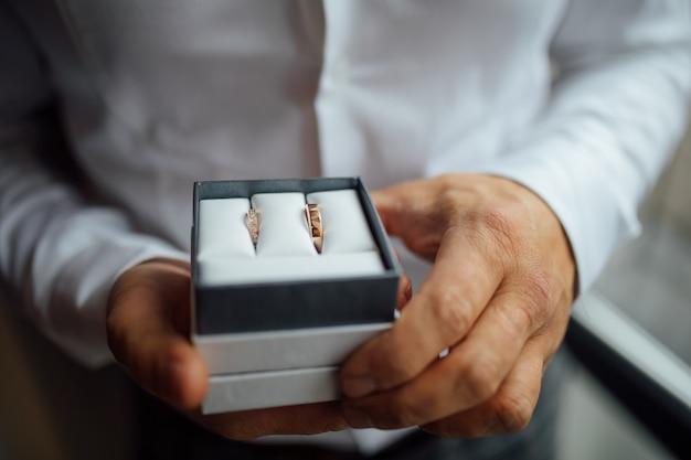 Золотые обручальные кольца в руках невесты.