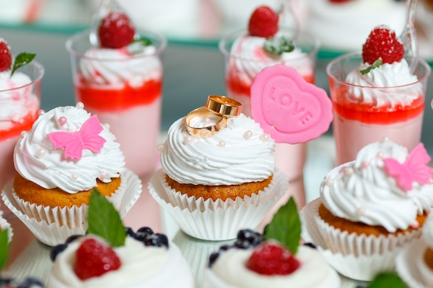 Gold wedding rings lie on the cute cupcakes