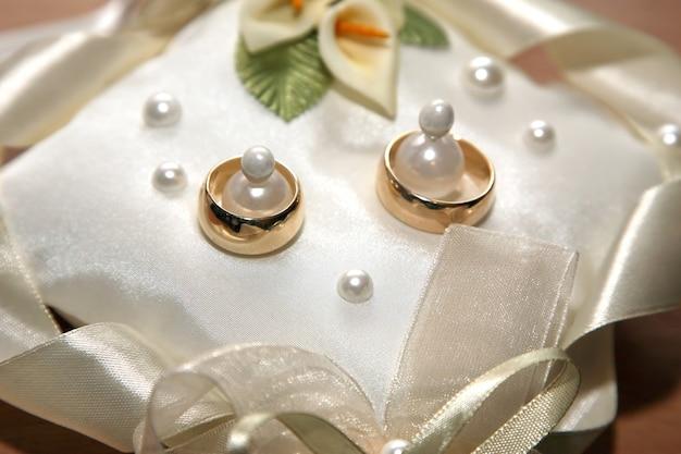 금 결혼 반지는 장식용 베개에 놓여 있습니다. 사랑과 가족 관계