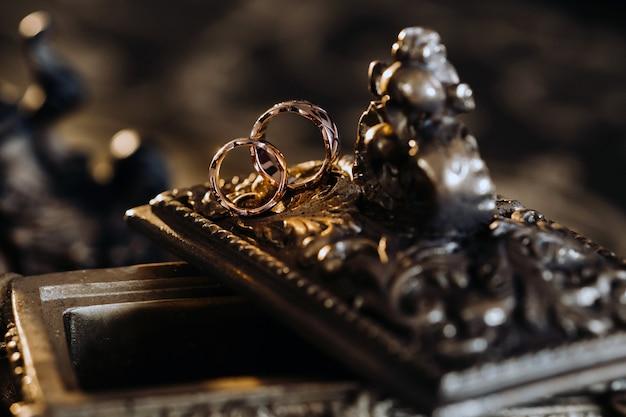 金の結婚指輪は、アンティークの宝石箱の上にあります。式典のための結婚指輪。