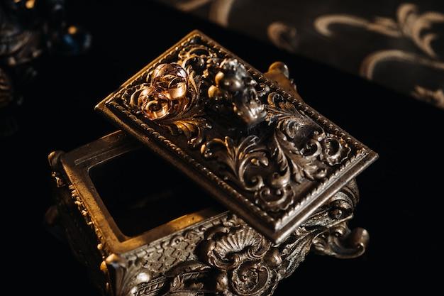 Золотые обручальные кольца лежат на старинной шкатулке для драгоценностей. обручальные кольца для церемоний.