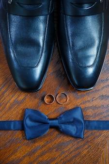 金の結婚指輪は、男性用の蝶ネクタイと靴の隣のテーブルにあります