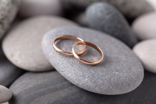 Gold wedding rings lie on the sea rock