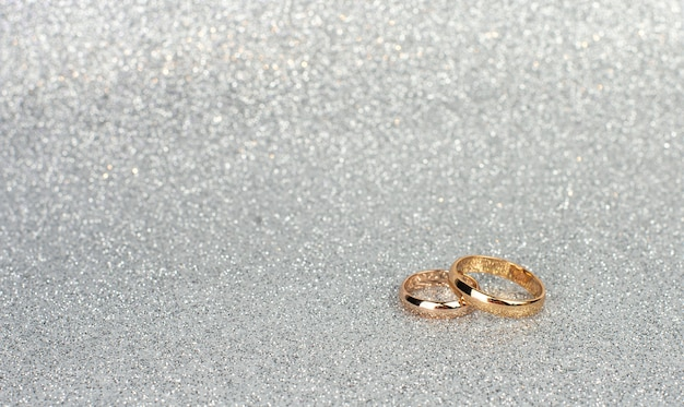 Gold wedding rings for newlyweds on a silver background with bokeh closeup