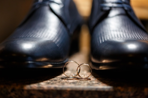 新婚夫婦の金の結婚指輪は、新郎のための紳士靴の隣にあります
