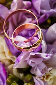 Золотые обручальные кольца на букет цветов для невесты