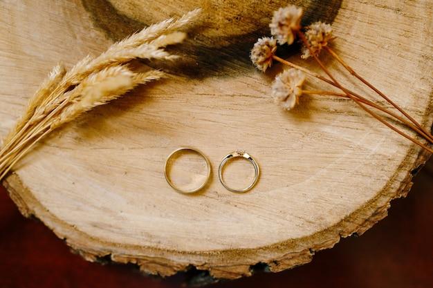 小穂とドライフラワーの木製カットにゴールドの結婚指輪