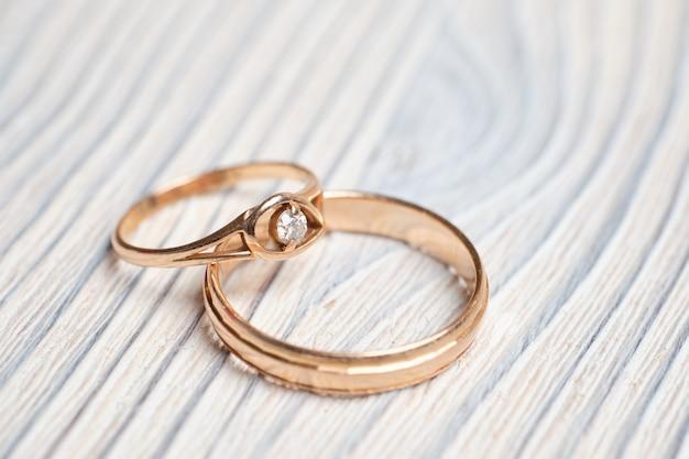 Золотые обручальные кольца на деревянном пространстве.
