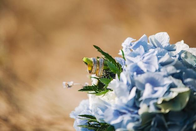 Золотые обручальные кольца на букете с красивой гортензией. копировать пространство