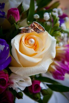 Золотые обручальные кольца на букет цветов