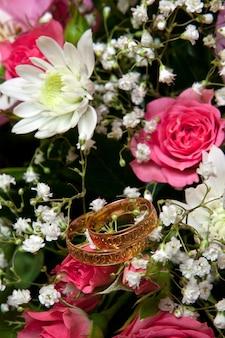 Золотые обручальные кольца на цветах