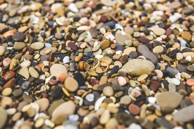 Золотые обручальные кольца на скалах пляжа.