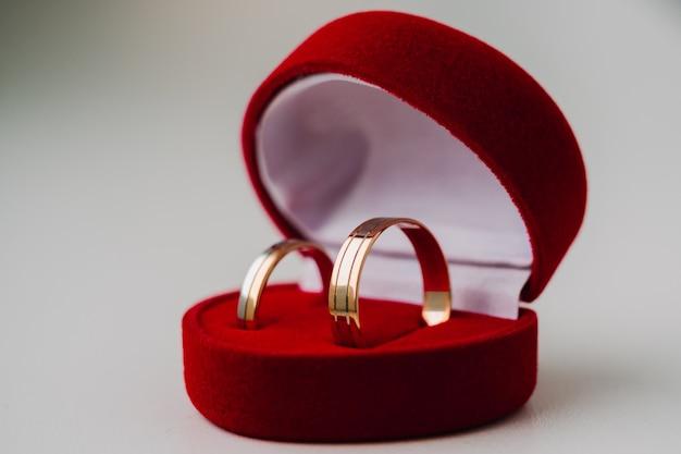 Золотые обручальные кольца, символизирующие любовь, в красной коробке в виде сердца на белом фоне