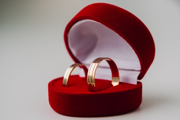 Gold wedding rings symbolizing love in red box as heart on white background
