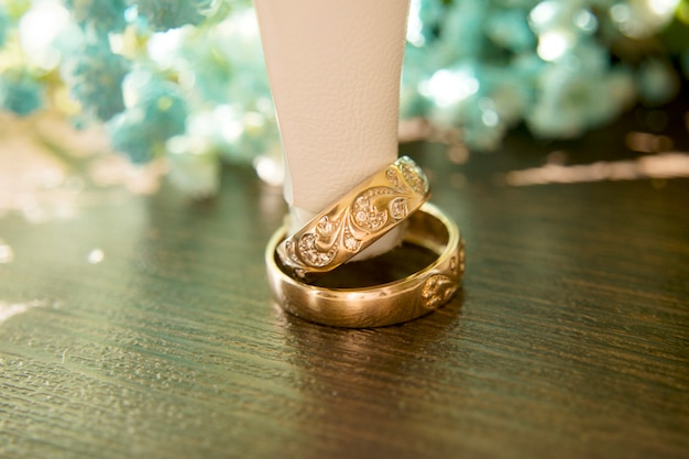 花嫁の靴のかかとの下に金の結婚指輪があり、背景には青いカスミソウの美しい花束があります。詳細、結婚式の伝統。閉じる。
