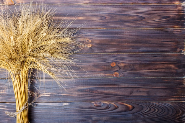 Gold wheat lying on a brown wooden surface with copyspace