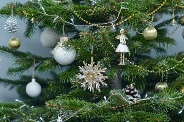 나무에 매달려 있는 금색 흰색과 은빛 크리스마스 장난감