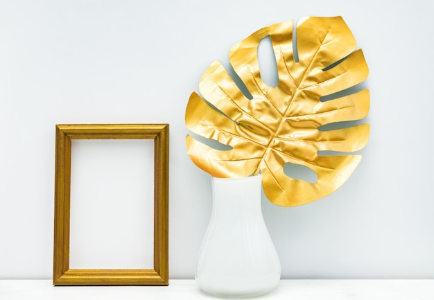 Gold and white interior mockup design. empty photoframe and monstera leaf im white vase on white wall background.
