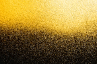 Golden abstract grainy texture on black background
