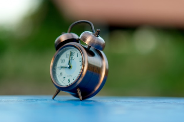 Golden alarm clock picture placed on a blue table, green background