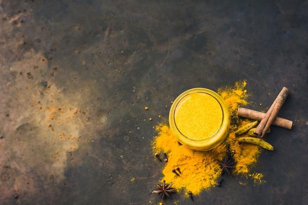 어두운 배경 클로즈업에 심황 가루를 넣은 황금 아몬드 우유 또는 호박 심황 라떼. 채식주의자를 위한 향신료가 포함된 트렌디한 아시아 천연 해독 음료 평면도