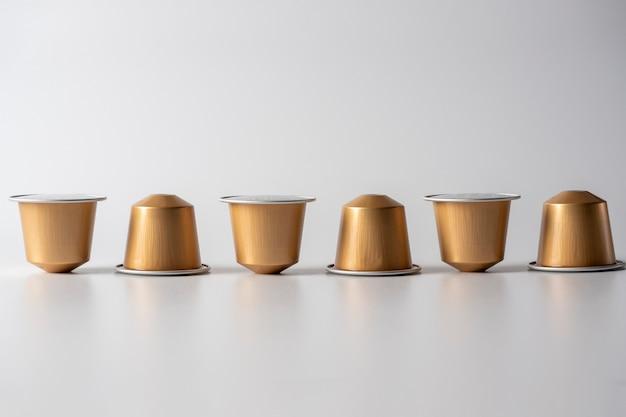 コーヒーマシン用の挽いたコーヒーと黄金のアルミニウムカプセルが白い背景の上に一列に表示されます