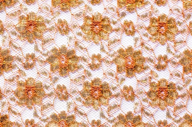 背景としての白い布の布の黄金と赤のレースのパターン