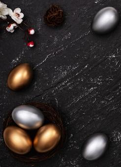 Золотые и серебряные пасхальные яйца с цветком сливы на фоне шиферного стола.