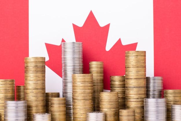 カナダの旗の前に金と銀のお金のスタック